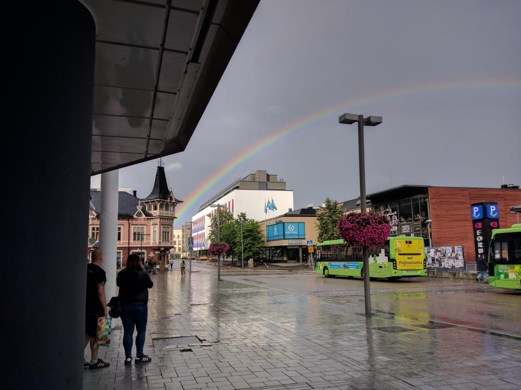 People taking photos of a rainbow at the bus terminal in the center of Jyväskylä, Finland.