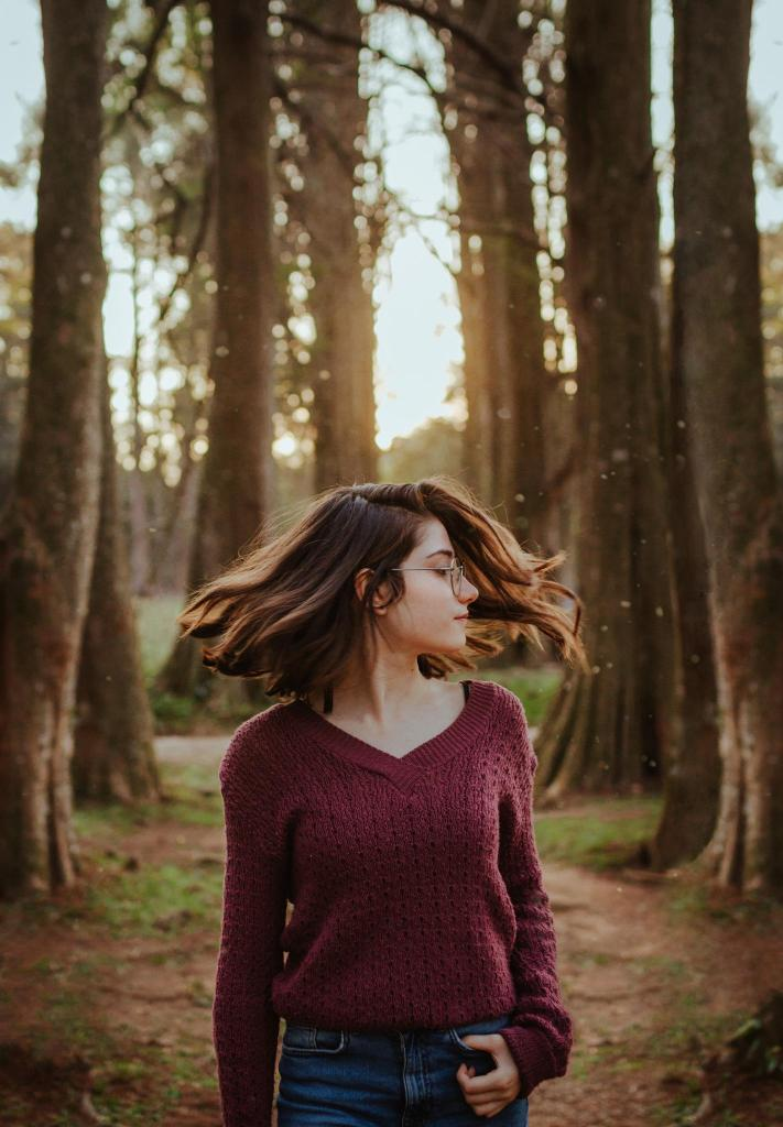 Woman enjoy green space, walking through the forest
