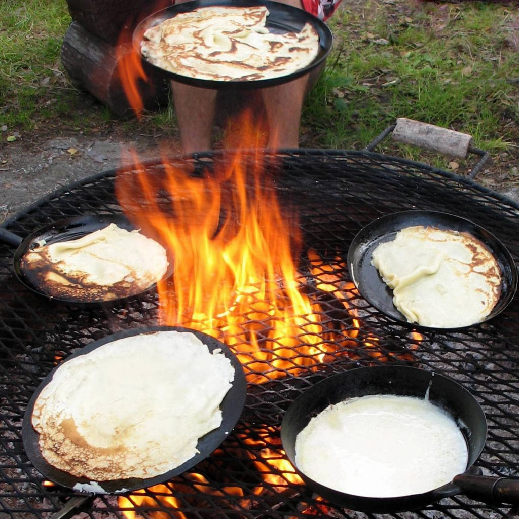 Lätyt or Pancakes being fried over a traditional nuotio or Finnish campfire.