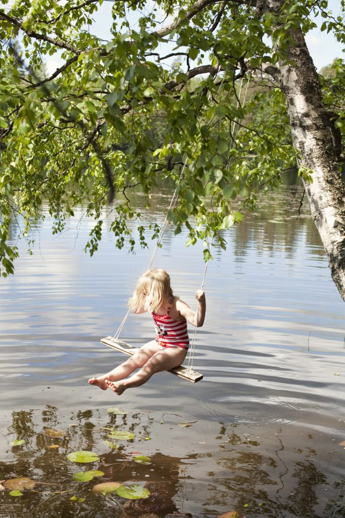 Child swinging on a tree swing over a lake during Juhannus/Midsummer