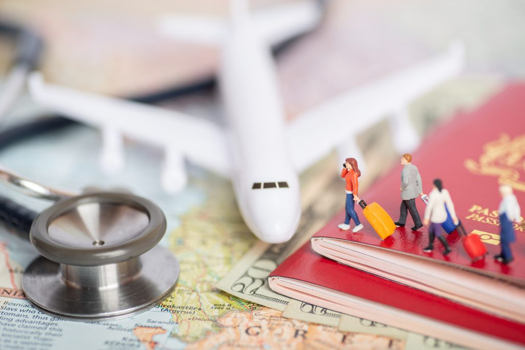 Medical tourism characterized as tiny traveller figurines, walking from passports atop bank notes to a toy plane beside a stethoscope. All are above a map laid upon wooden furniture.