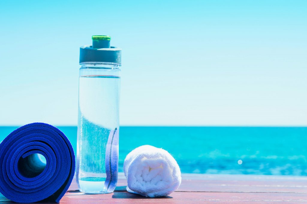 A rolled yoga mat and towel with a water bottle between them serve to illustrate preparation to avoid sports injury during summer